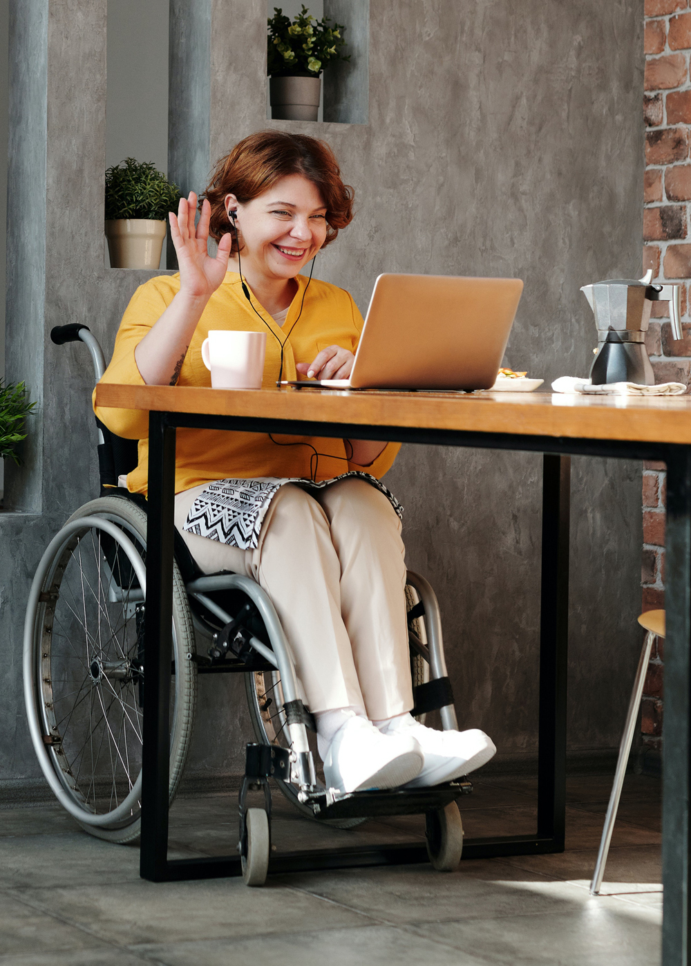 Woman using a wheelchair, by a table talking via a computer, waving her hand and smiling
